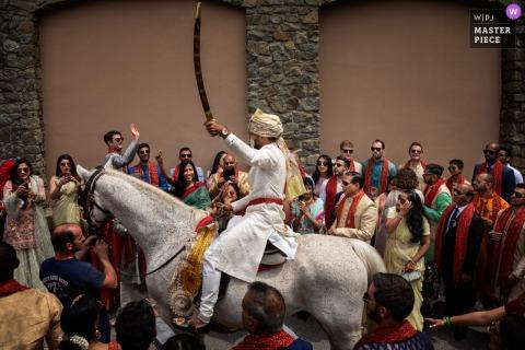 Renaissance Tuscany Il Ciocco Destination Indian wedding photograph of groom arriving on horseback with sword raised