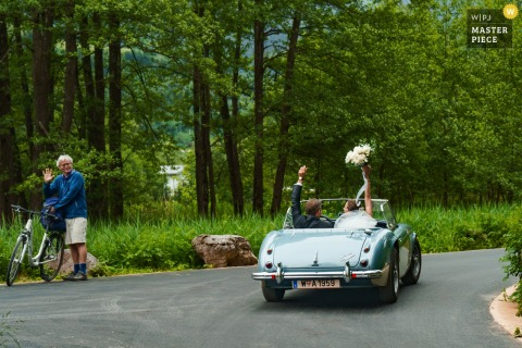 Zell Am See, Schloss Prielau, Austria Photo of bride and groom driving away in convertible car after wedding ceremony.