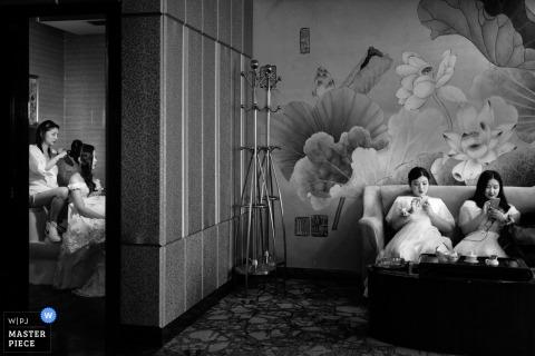 Druhny siedzą w innym pokoju, podczas gdy panna młoda robi sobie włosy na czarno-białym zdjęciu autorstwa fotografa dokumentalnego Fujian w Chinach.