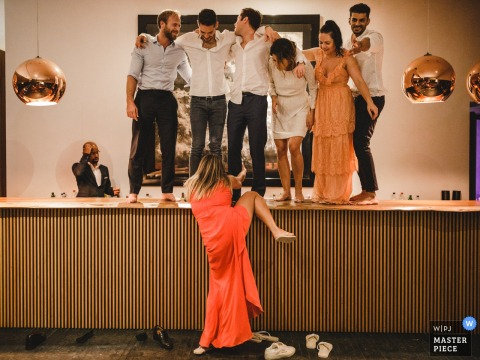 A woman tries to climb up onto the bar with other guests at Land Vineyards in Montemor-o-Novo in this wedding photo composed by a Portugal photographer.