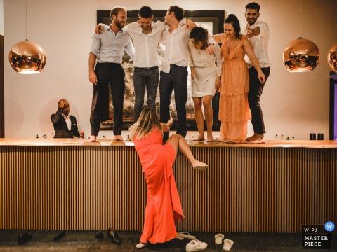 Une femme tente de grimper sur le bar avec d'autres invités à Land Vineyards à Montemor-o-Novo dans cette photo de mariage composée par un photographe portugais.