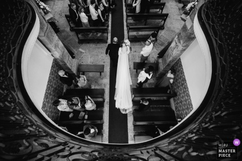 The bride and her father walk down the aisle to the altar in Quinta dos Pinheirais in this photo taken from above by a Portugal wedding photographer.