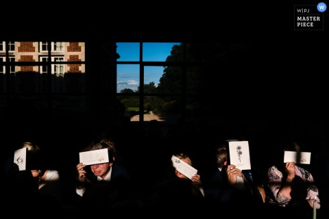 Dinner guests are blinded by the evening light and use the menu cards to hide their eyes in this Kasteel Ter Block wedding ceremony photograph.