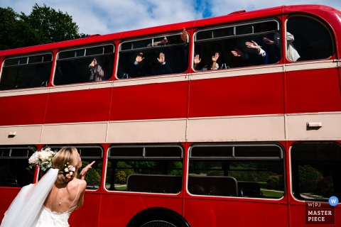 Wedding Photo at Kasteel Ter Block | Bride blows kisses to her waving guests that arrive in a ceremony bus