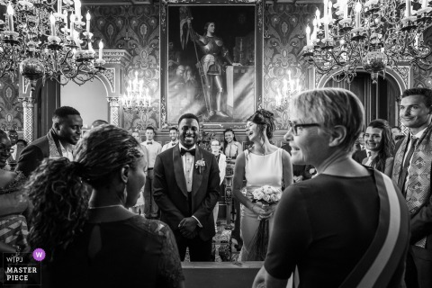 The bride laughs at a joke as she and her groom stand at the altar in Orleans in this black and white photo by a France wedding photographer.