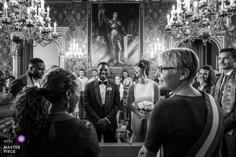 De bruid lacht om een grapje terwijl zij en haar bruidegom in Orleans op het altaar staan in deze zwart-witfoto door een huwelijksfotograaf uit Frankrijk.