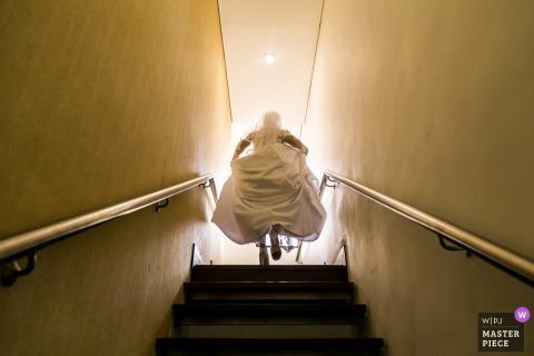 Die Braut geht eine Treppe hinauf ins Licht von Caracas in diesem Bild, das von einem venezolanischen Hochzeitsfotografen im Stil eines Dokumentarfilms aufgenommen wurde.