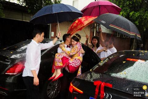 Drużbowie niosą pannę młodą i trzymają nad nią parasole, aby utrzymać ją suchą w deszczu na tym obrazie w stylu dokumentalnym skomponowanym przez fotografa ślubnego z Huizhou w Chinach.