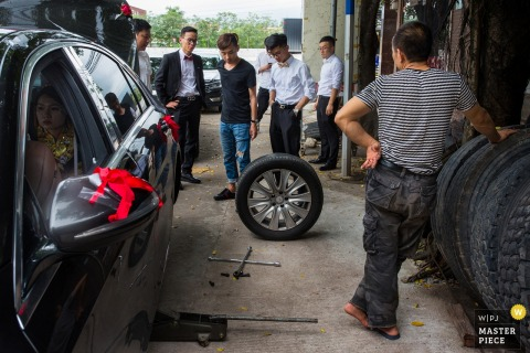 Groomsmen take a car to a mechanic to change a tire in this photo taken by an award-winning Huizhou, China wedding photographer.