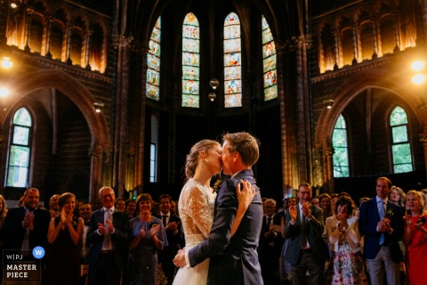 Photograph of the bride and groom kiss during the ceremony at Vondelkerk Amsterdam