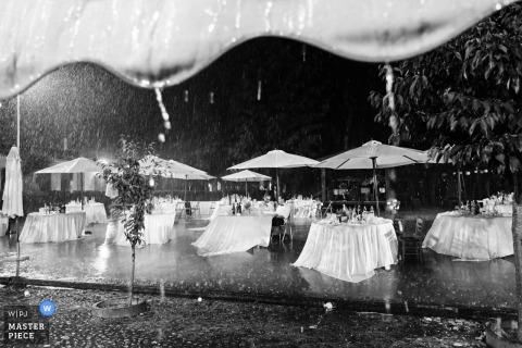 Las mesas de recepción vacías se sientan afuera en una tormenta en la Cascina Pietrasanta en esta imagen en blanco y negro creada por un fotógrafo de bodas documental de Lombardía.