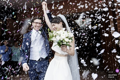 Magenta - cascina Pietrasanta wedding photo of bride and groom under confetti hearts storm