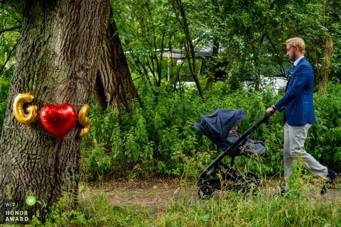 """Kabels w """"de Westerbouwing"""" Oosterbeek - Pan młody próbuje usnąć swoje dziecko w wózku po sesji karmienia piersią. Jednak z powodu wielu rozproszeń ich dziecko nie zasnęło, ponieważ wygląda ciekawie z wózka jako inicjacja"""