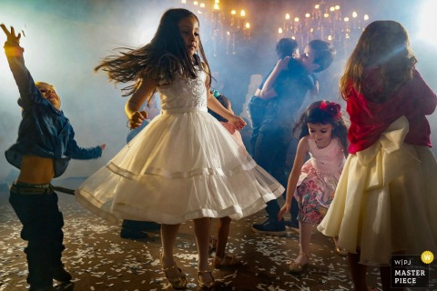 Children dance during the reception at the Casamento Talita e Marcos in this image composed by a Goias, Brazil wedding photographer.