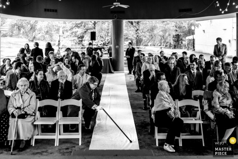 Glen Echo Park, Maryland Wedding Ceremony Photograph of a guest straightening up the bride's aisle runner