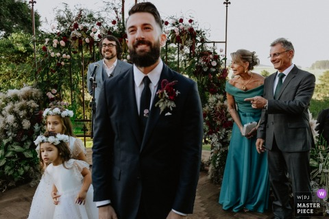 The groom waits for the bride at the altar at Vinicola Laurentia in this documentary-style wedding photo by a Rio Grande do Sul, Brazil photographer.