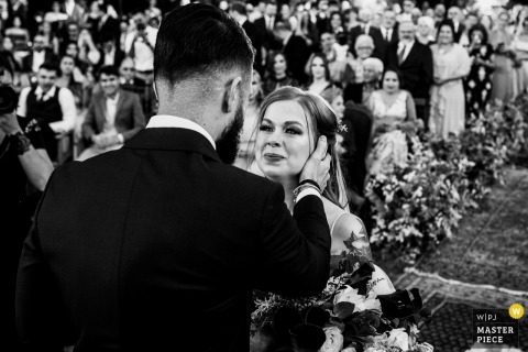 The bride and groom stand at the altar together during their wedding at Vinicola Laurentia in this black and white photo composed by a documentary-style Rio Grande do Sul, Brazil photographer.