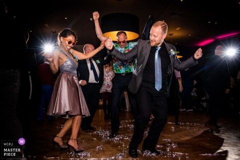 Los invitados disfrutan bailando en la pista de baile durante la recepción en esta imagen capturada por un fotógrafo de bodas de Overijssel, Países Bajos.