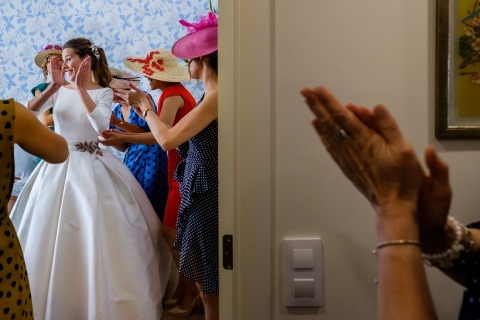 Guests applaud the bride in this getting ready image composed by a documentary-style wedding photographer.
