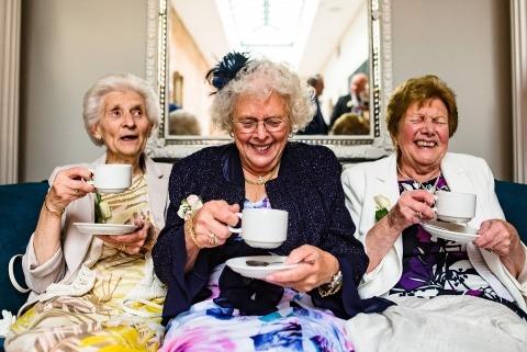 Photographie de reportage à la réception de mariage montrant des dames buvant du gin dans des tasses à thé