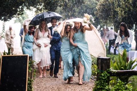 Foto van de bruid en bruidegom met de gasten gevangen in de regen op zoek naar dekking.