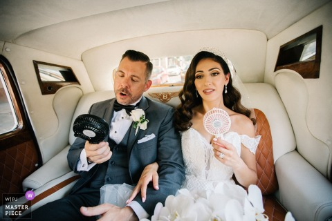 "Hyatt Sacramento Wedding Photographer: ""It was so hot that day"" Bride and groom with fans in the back of the limo"