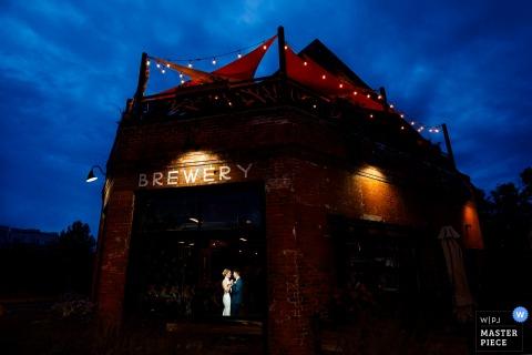 一起分享他們的第一個舞蹈的新娘和新郎照片在他們的結婚宴會期間在野薔薇共同的啤酒廠在丹佛,科羅拉多。