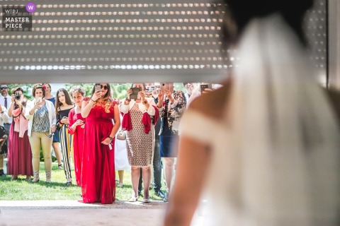 Chateau de Malliac wedding photo of bride revealing dress as door rolls up