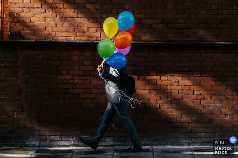 Royal Hospital Chelsea Wedding Photo as A Groomsmen walks past some lovely light with some colourful balloons