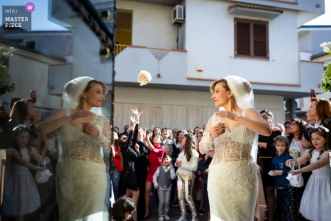 The bride turns toward her reflection as she tosses her bouquet over her shoulder in front of the Villa Blanche in this wedding photo composed by a documentary-style Calabria photographer.