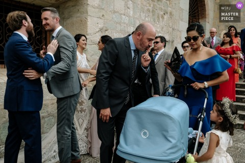 Photography after ceremony in Santo Domingo de Guzman, Oaxaca, Mexico | Wedding guest hushing little girl next to a sleeping baby