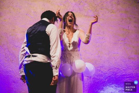 Braut und Bräutigam spielen ein albernes Spiel während ihres Empfangs in Montecarlo auf diesem Hochzeitsfoto, das von einem Fotografen aus Pistoia, Toskana, verfasst wurde.