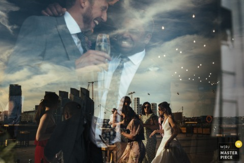 Wedding Photography from Trinity Buoy Wharf | Wedding guests and bride refelected in window