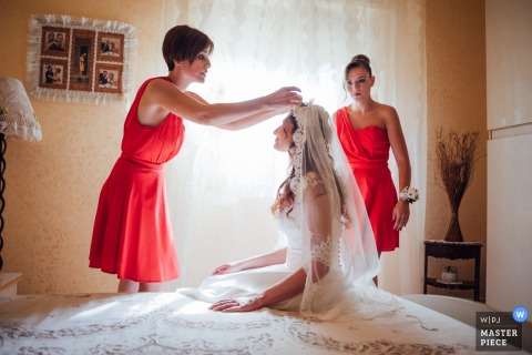 Reggio Calabria - Royal Garden Wedding Photography | The bridesmaid arranges the veil of her best friend