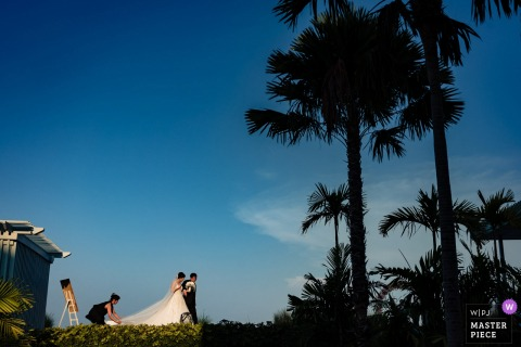 Bride and her dad head for the outdoor ceremony under the palm trees in Phuket, Thailand