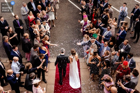 Guests toss confetti at the bride and groom as they exit their London, England ceremony in this image captured by a Phuket, Thailand wedding photographer.