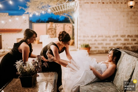 Helotes, Texas - The Oaks at Heavenly Photography - Mother and sister of the bride help add her garter in a humorous moment