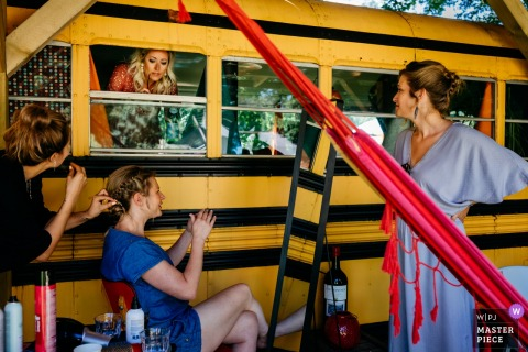 Women get ready for the ceremony by a school bus at Camping de Lievelinge in this picture created by a documentary-style Utrecht, Netherlands wedding photographer.