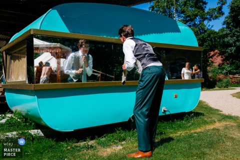 The groom checks his outfit in a caravan mirror, bride is watching at Camping de Lievelinge