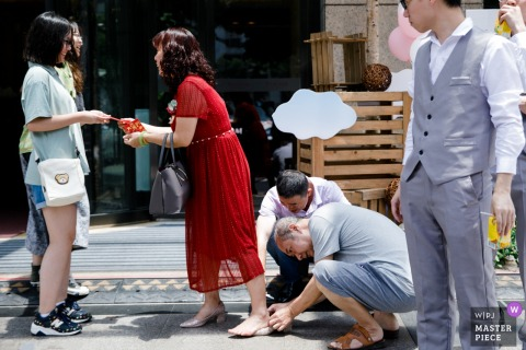 A man puts a bandage on a woman's heel in this wedding photo by a Fujian, China documentary photographer.