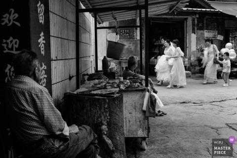 A man watches the wedding party proceed from afar in this black and white wedding image by a documentary Fujian, China photographer.