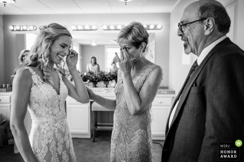 French Creek Golf Club wedding venue photo | Bride seeing her father for the first time in her dress while her mom stands by her side.