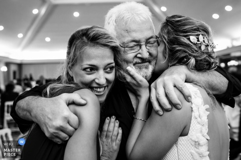 A father hugs the bride and her sister at El Puig in this black and white photo by a Valencia, Spain documentary wedding photographer.