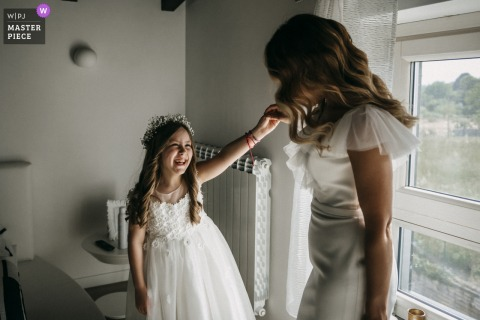 The bride raises the flower girl's arm to get a better look at her dress before her wedding at Le Chiacchiere Artena in this image composed by a documentary-style Lazio photographer.