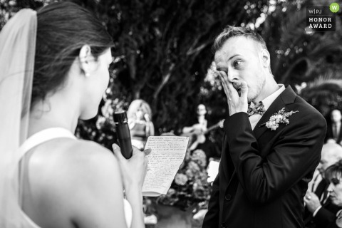 Villa Il Pizzo outdoor wedding ceremony photography - Groom tears during vow exchange.