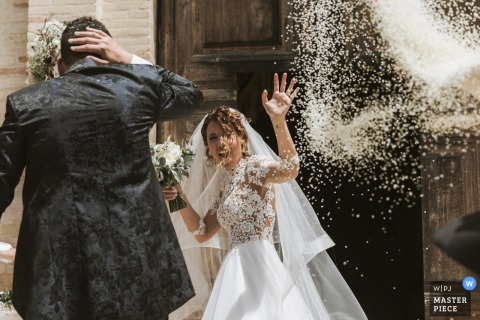 Chiesa Santa Croce Mogliano photograph of the rice throwing at bride and groom after church ceremony