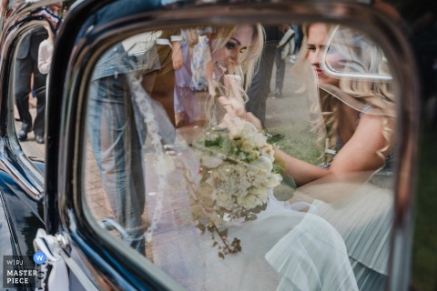 The bride is photographed through the car window as she exits her Kirche Bollensen Uslar ceremony in this award-winning photo by a Hagen, North Rhine-Westphalia wedding photographer.