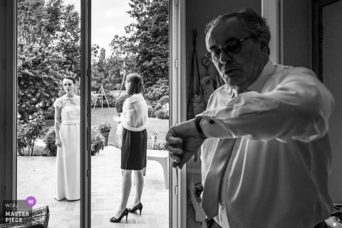 A man checks his watch before the ceremony in Checy in this black and white wedding photo composed by an award-winning Val de Loire, France photographer.