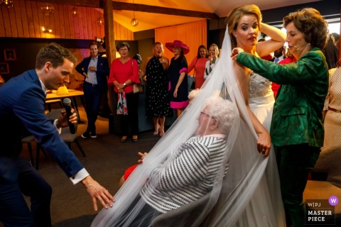 A bride accidentally drapes her veil over a guest at her Delden - Hoeve de Haer wedding in this photo captured by an award-winning Overijssel, Netherlands photographer.