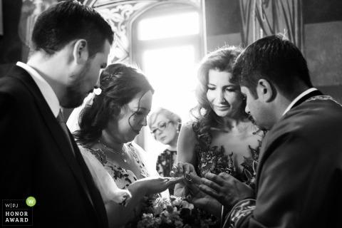 Foto de la boda de la iglesia de Corbeanca: la madrina se pone el anillo en el dedo de la novia mientras la novia madre mira desde atrás durante la ceremonia ortodoxa